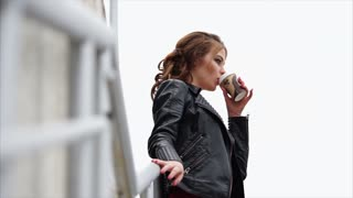 Urban scene of beautiful young brunette in leather jacket drinking coffee. Good way to refresh in the morning
