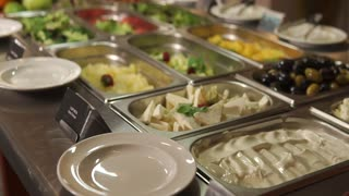 Vegetarian meals on a buffet in a restaurant. Vegetables and herbs is lying in plates, fruits, olives and cut cheese