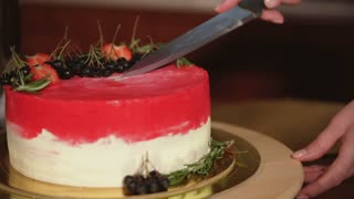 Waiter is making an incision in sweety cake standing on a table. She is using dessert knife and putting it inside