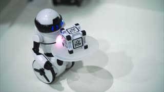 White little robot waiter carrying little cube and balancing. Concept of electronic robot toys. Close up view