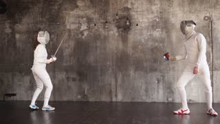 Woman and man are engaging in sporting fencing with rapier. They are learning attacks and protections, preparing for olympic games