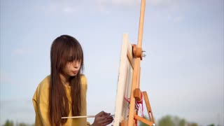 Woman artist painting with oil on canvas en plein air. Young impressionist creating landscape working outdoor by the lake