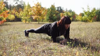 Woman having regular sport training. She working out in autumn park and doing plank exercise