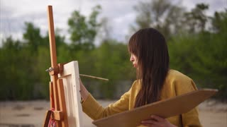 Woman impressionist painter working under her piece of art en plein air. Painting landscape from life