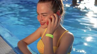 Woman in the resort at swimming pool with smartphone. She using her cell phone to talk to her friends. Modern technology in our life