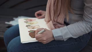Woman is drawing pictures sitting on a bench outdoors. She is using multicolor pencils, close-up of hands and paper on knees