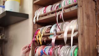 Woman is trying different ribbon for packaging, extending it from rack. She is choosing one red tape and cutting a piece of it