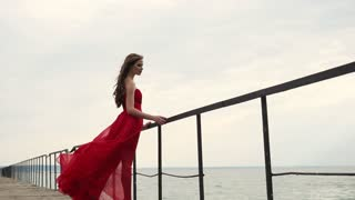 Woman is wearing chic red dress is enjoying view of sea in cloudy windy day. She is standing on a long wooden pier, holding old handrails, side view