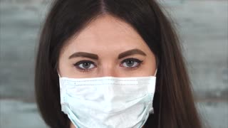 Woman nurse straighten her protective medical mask. Concept of different professions. Close up view
