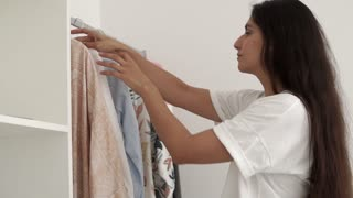 Woman preparing to go out and picking clothes for outfit. Going through clothing rack in the room. Beautiful stylish blouse.