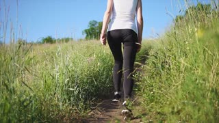 Woman walks up the path on a hill studying nature as a tourist. View from the back. Close up shot of the woman's legs.