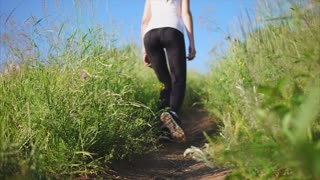 Woman walks up the path on a slope with a wild green grass. Female discover the nature, walk in the fresh air as a tourist. View from the back. Close up shot of the woman's legs. Selective focus.