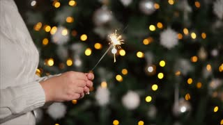 Woman waving a sparkler at the party against Christmas tree. Holiday celebration