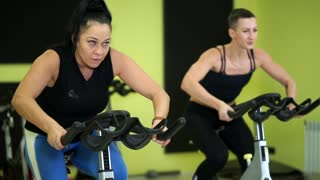 Women are actively engaged in group bike training to maintain physical fitness. Cicle training is a good cardio load on the body of athletes before the upcoming physical exercises.