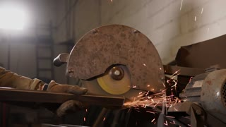 Worker is processing corners of metal beams. He is holding it and pressing to rotating disc of old grinder in a worksop