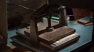 Worker making a stamp on leather using embossing press machine