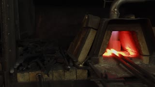 Working forging kiln with two billets inside. Flame is burning and warming, prepairing stage in processing of metal in a forge