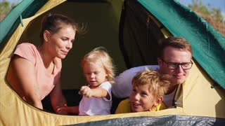Young and beautiful people are sitting in a tent, the husband and her husband enjoy the view of nature, their children are smiling, the family left for nature at the weekend