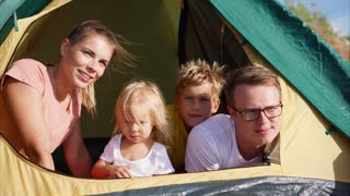 Young and beautiful people are sitting in a tent, the husband and her husband enjoy the view of nature, their children are smiling, the family left for nature at the weekend. . . . . .