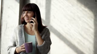 young and beautiful woman drinks hot coffee from glass, lady holds a cup of drink in her hand and smiles while talking on smartphone with her girlfriend