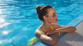 Young and beautiful woman who wears a swimsuit resting in the pool on a sunny day, the lady in sunglasses relaxes in blue and cool water during the holidays