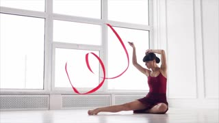 Young athlete girl is rehearsing her rhythmic gymnastic performance with ribbon. Elegant pose and sporty body of pretty brunette woman in a white room