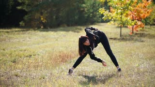Young athletic woman working out in autumn park. She doing bend twist exercise. Keeping fit and healthy