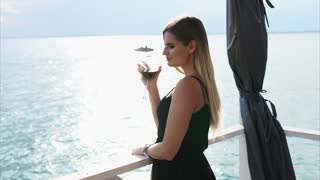 Young attractive woman is standing on the outdoor restaurant terrace. Wearing black dress, she is drinking red wine and enjoying the view of the sea.