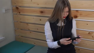 Young beautiful business woman with long hair is looking interested in a mobile phone. The girl's hand is wearing a smart watch, it seems she is following the novelties in the world of technology