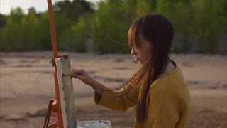 Young beautiful woman painter drawing picture of abstract landscape with oil paint and brush. WIndy weather