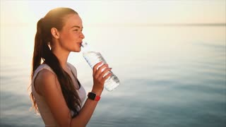 Young brunette woman drinking a clean water from the plastic bottle standing near the sea after sport activity. Female wear smart watches. Concept of water balance. Strong back light and lens flare.