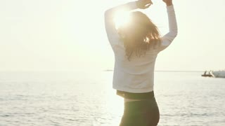 Young brunette woman is rejoicing and spinning around herself on beach in sunset time. She is having fun alone, moving hands against the sun
