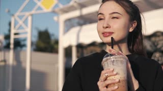 Young brunette woman is tasting ice coffee, sipping it from a straw. Standing outdoors in summer evening, close-up of hands and face. Concept of lifestyle.