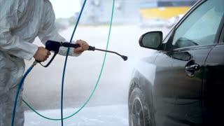 Young caucasian man washes his car carefully. Car washing self-service. Water spray machine.