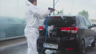 Young caucasian man washing his car using water spray on the car wash self-service. Car washing with water. Water spray machine.