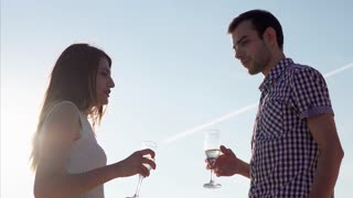 Young couple clanging glasses and drinking wine against sky and sunshine
