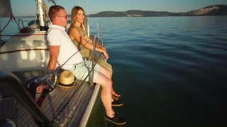 Young couple having enjoyable water travel at sunset. Man and woman sitting on the yacht board and talking