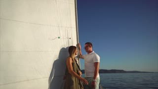 Young couple of lovers is on a romantic boat with large white sail. They are looking to each other with love, touching hands and smiling.