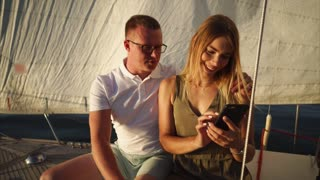 Young couple on the front deck of sailing yacht. Woman using mobile to look at photos they made during the sea trip