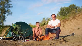 Young couple spending holidays in the countryside. They sitting near the fire and talking. Camping with tent