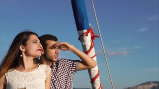 Young couple traveling by yacht. Man showing something to the woman and they both looking into distance hiding from the sun with hands