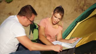Young family couple looking at the countryside map sitting by the tent. Camping holiday