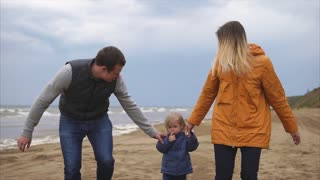 Young family enjoying walking on the beach. Man, woman little girl and boy. Mother and father holding girl in hands. Happy times together