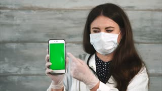 Young female doctor in face mask and gloves with chroma key cellphone. She pointing at the screen