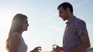 Young friends, possibly woozy talking on a yacht during the day, a man and a woman are drinking drinks from glass glasses, a couple is riding a ship on the sea