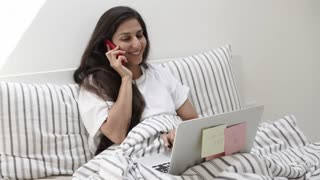 Young girl is chatting by mobile phone in morning and working with notebook. She is sending email in start of day, lying in bed