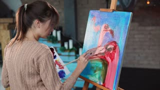 Young girl is drawing birds by oil colors in canvas. She is taking paint from palette by brush and laying on canvas, studio of contemporary talent creative person.
