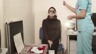 Young girl with phoropter during sight testing or eye examinations in ophthalmological clinic. Trying different lenses.