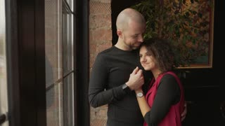 Young happy couple stand near the panoramic window in the cafe.
