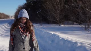 Young happy woman walking in the winter street.